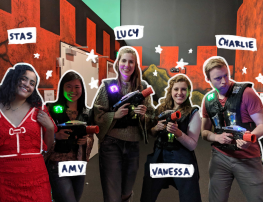 [The Social Cipher team of four women and one man are in a row posing with laser tag vests and blasters]