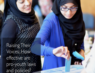 The image is the cover of the report and consists of two girls standing side by side in front of a ballot box. The girl on the left is smiling while the girl on the right places her vote in the box. On the bottom left side of the image the title Raising their Voices: How effective are pro-youth laws and policies? is written in a text box.